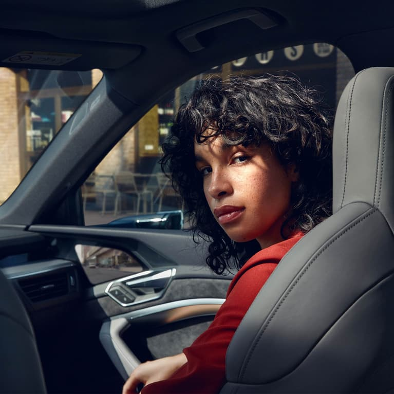 Woman looks back over her shoulder from the passenger seat of an Audi e-tron Sportback